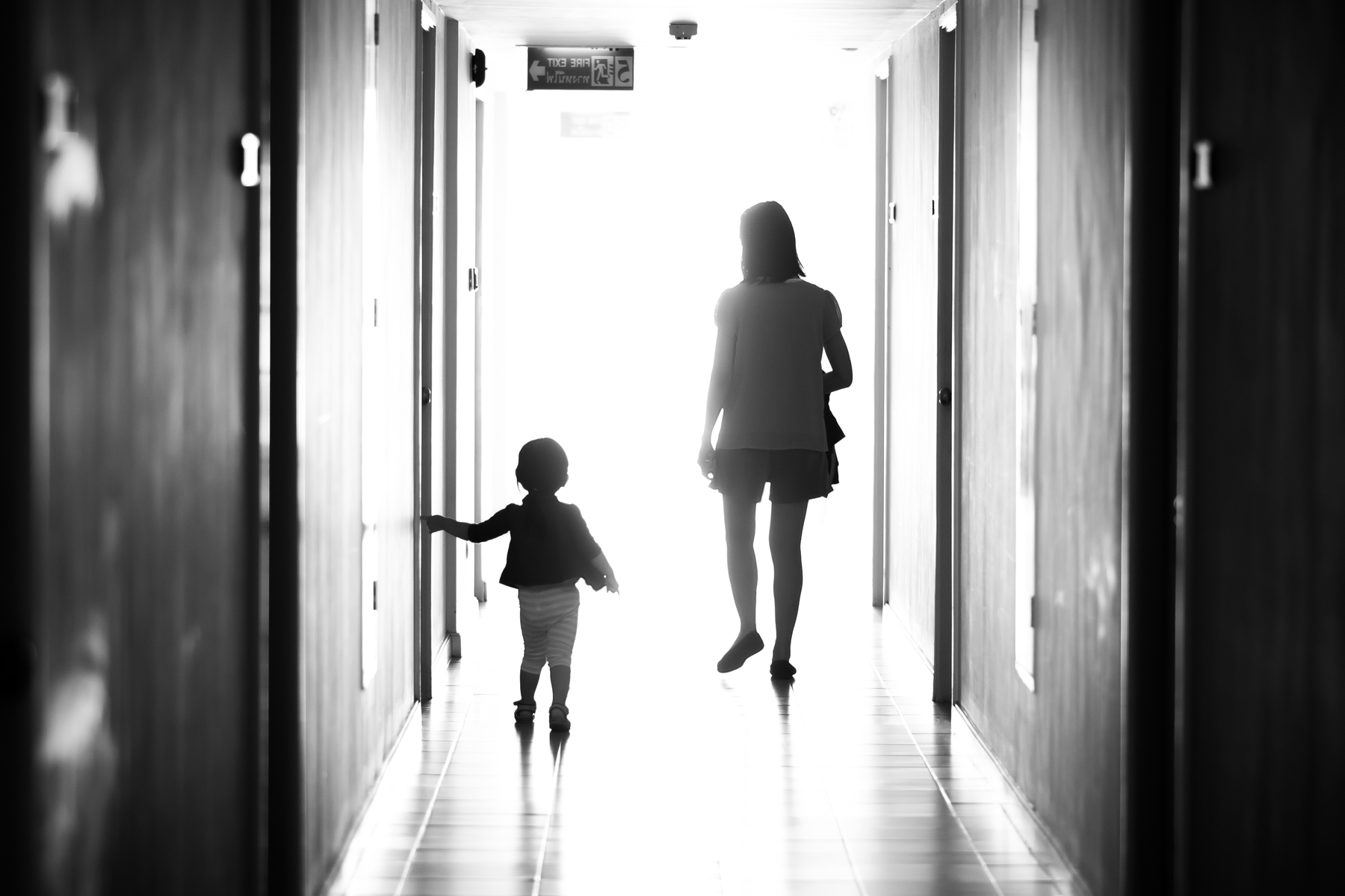 Mother and child walking down hallway