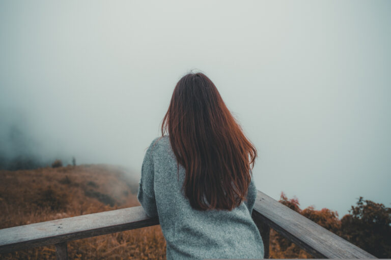 Woman standing alone looking at fog