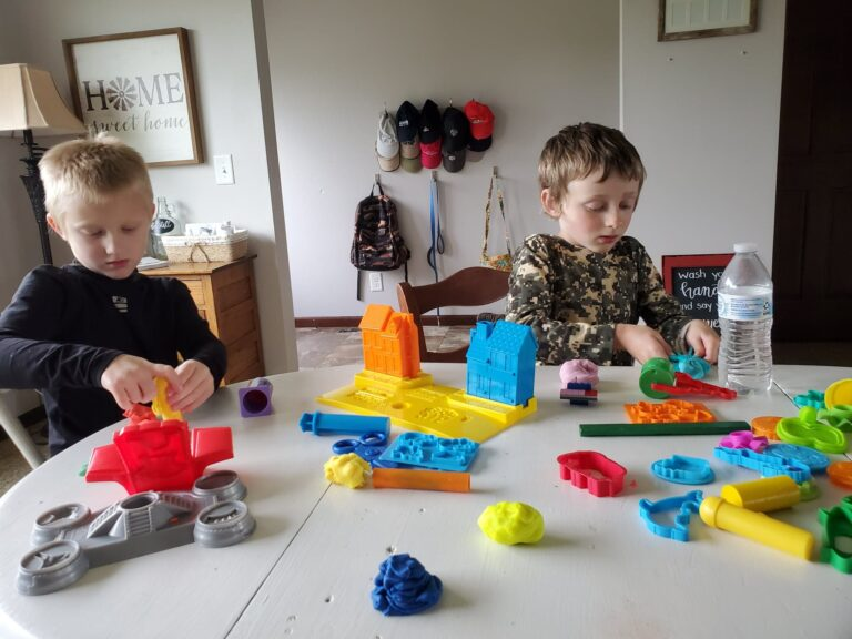 Little boys playing with Play-Doh, color photo