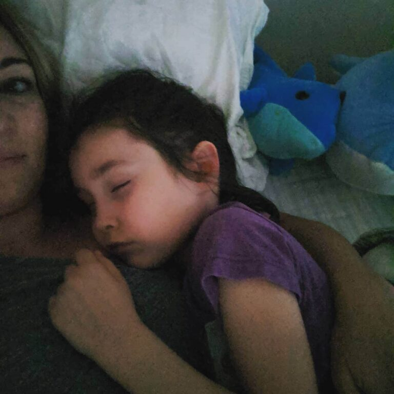 Little girl asleep in her mother's arms, color photo
