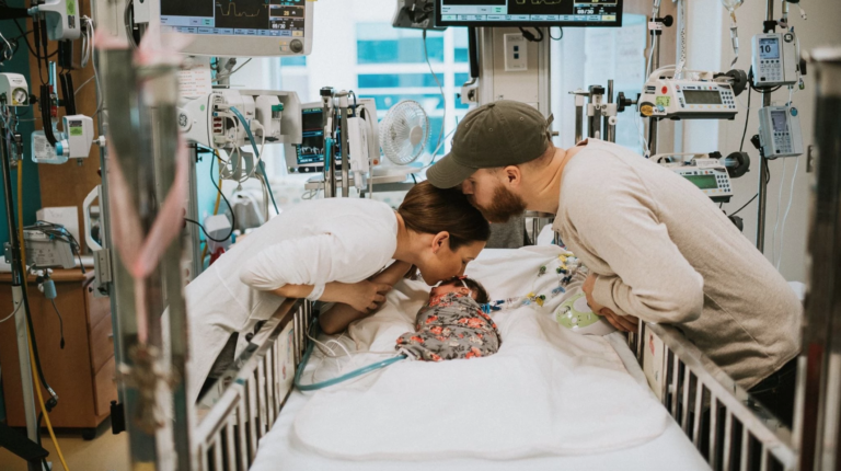 Mother and father kissing baby in hospital bed