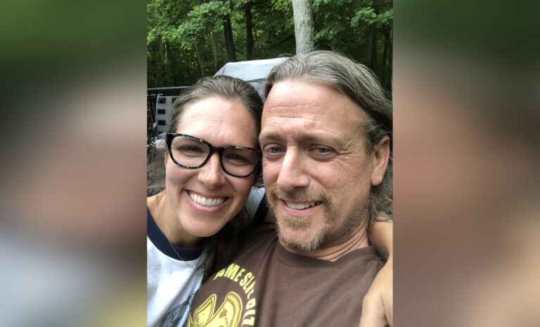 Couple smiling with arms around shoulders, color photo
