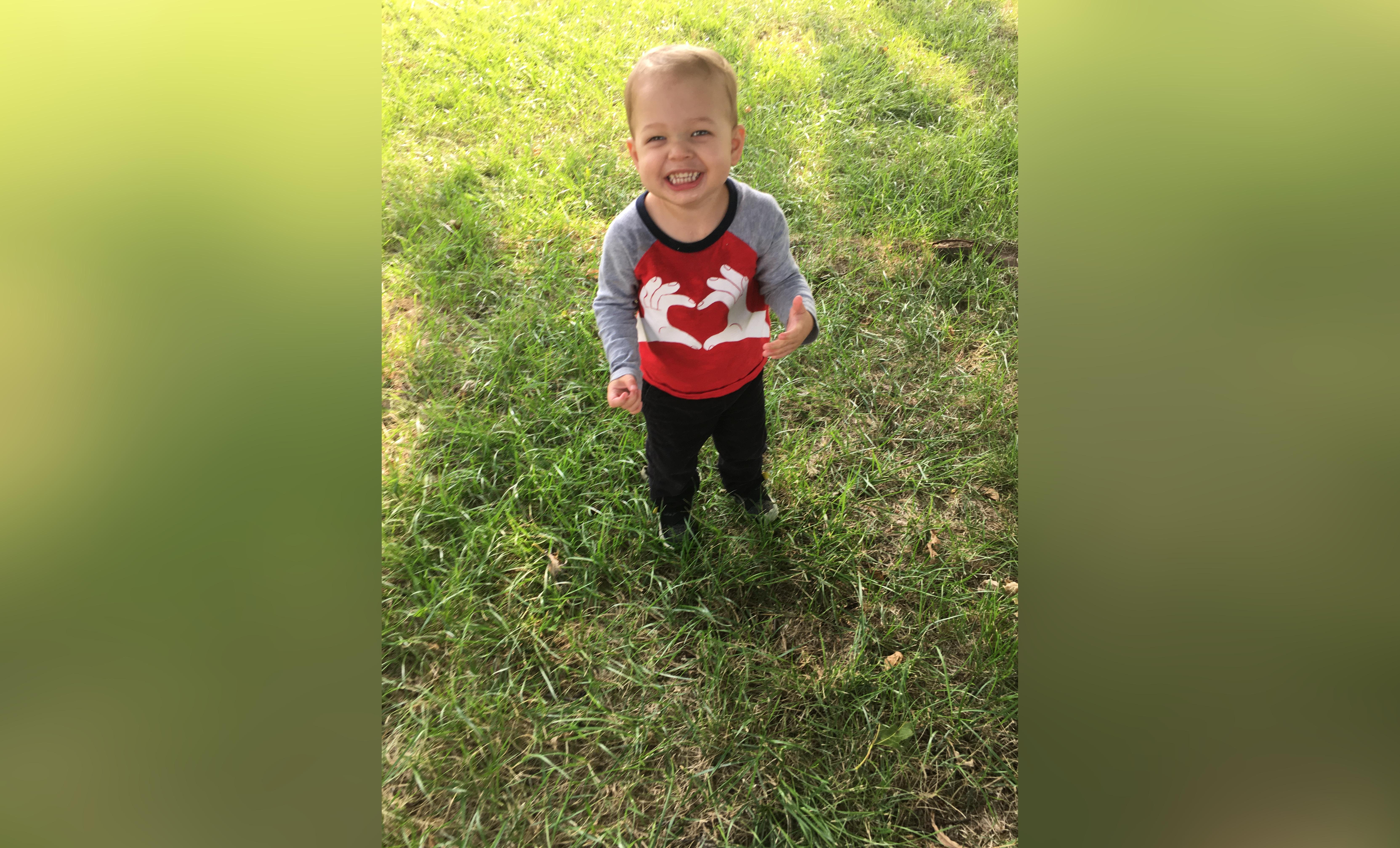 Little boy smiling outside, color photo