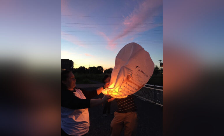 Woman holding memorial lantern, color photo