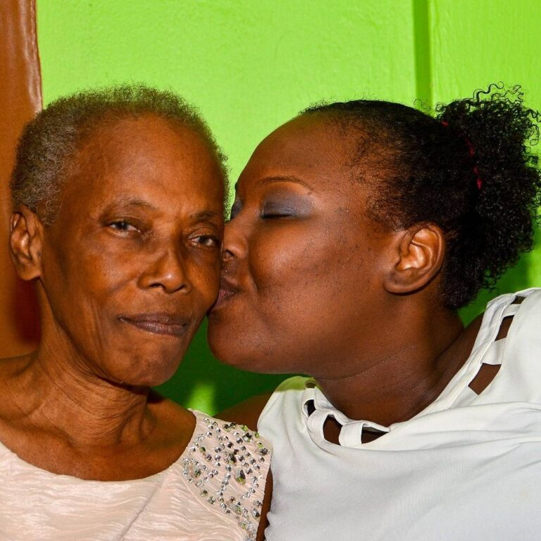Grown daughter kissing mother