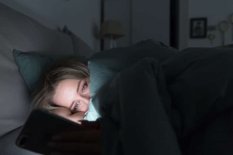 Woman with insomnia looking at phone
