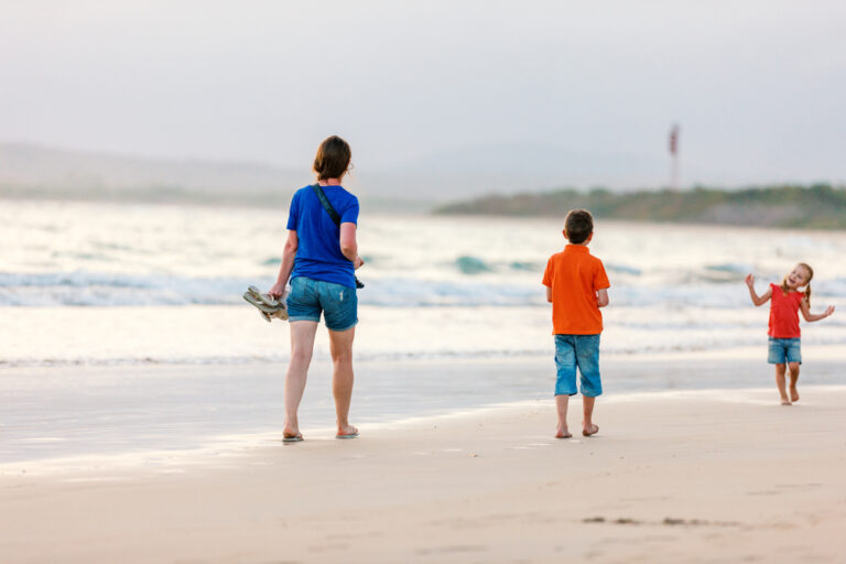 Woman walking on beach with kids