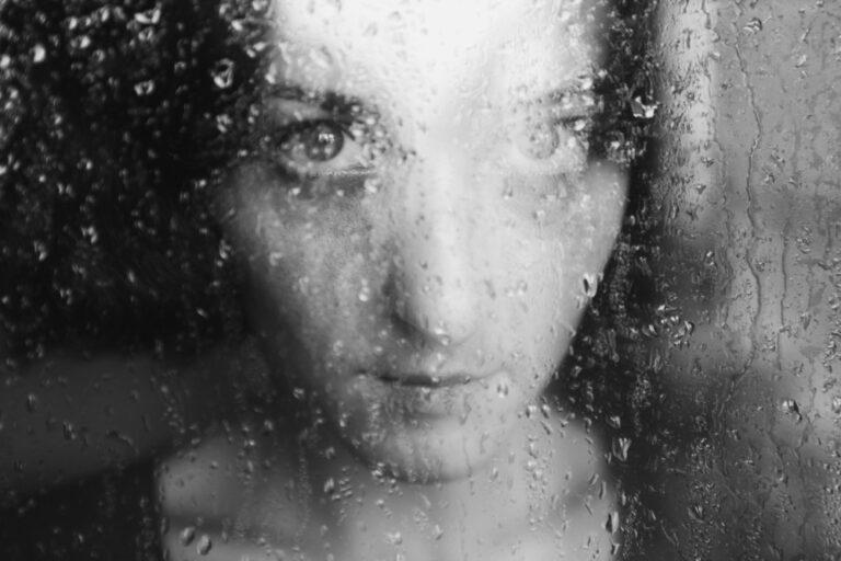 Sad woman through window