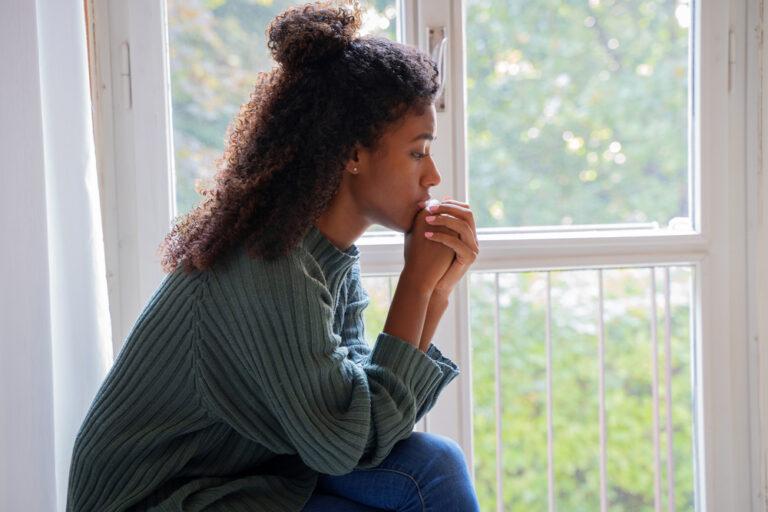 Woman praying by window
