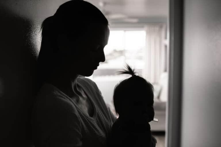 Tired mom holding toddler