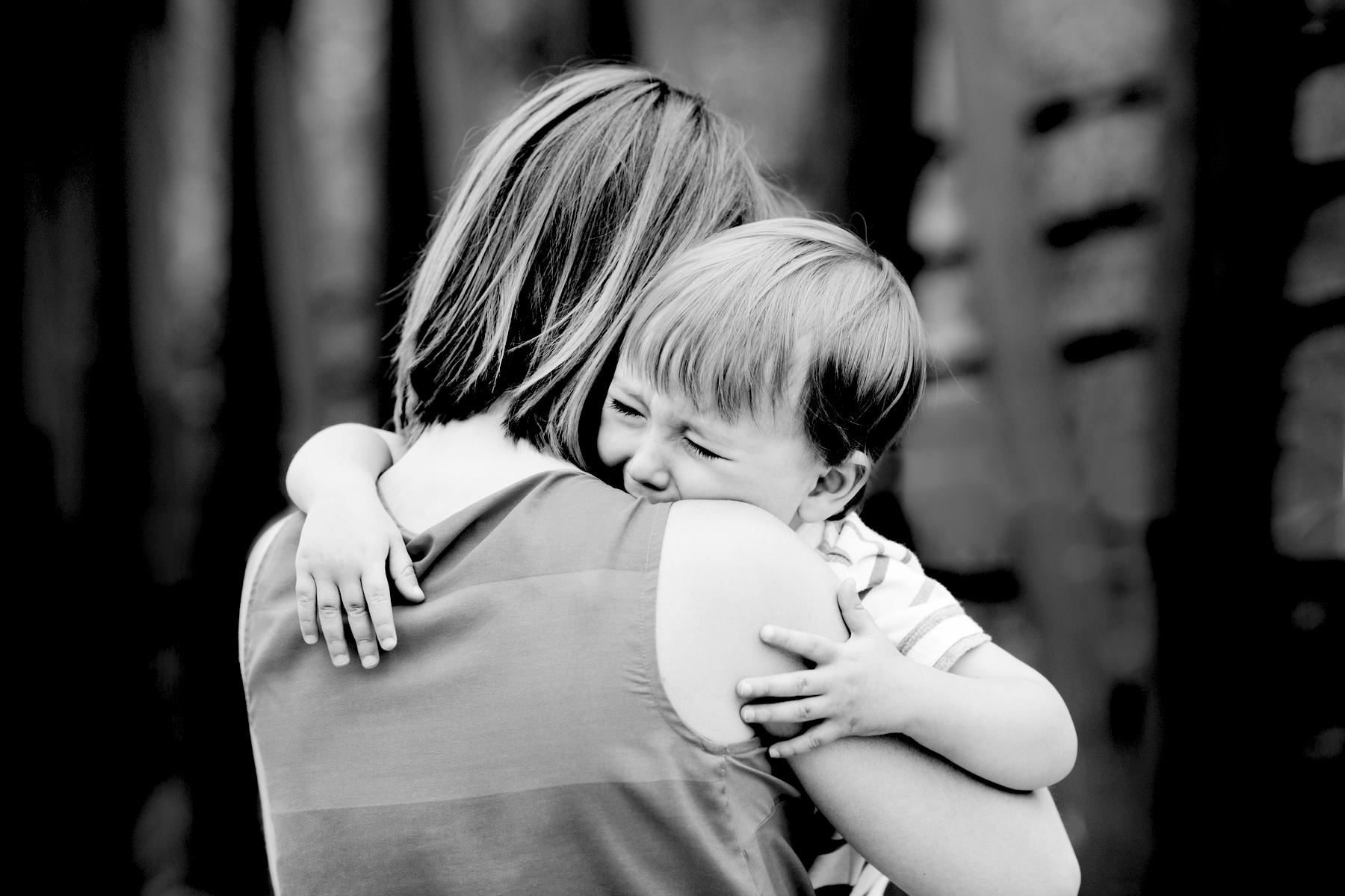 Mom hugging crying boy