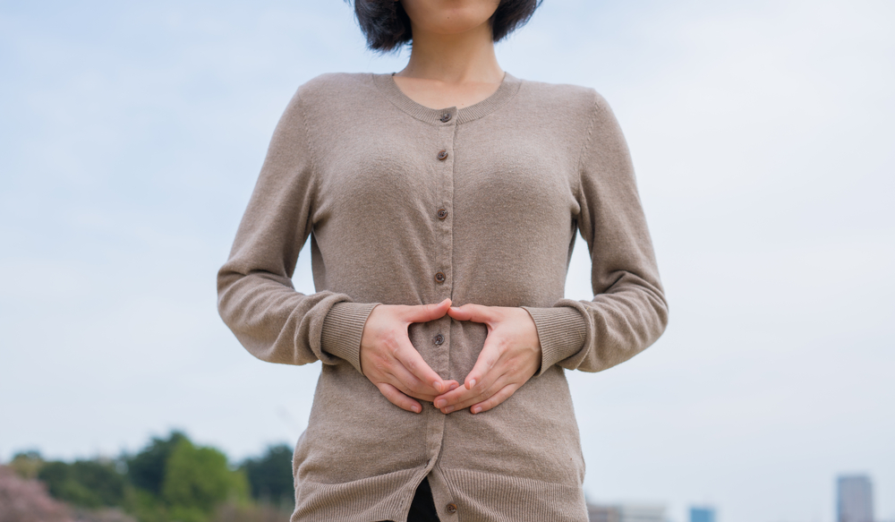 Woman making heart over stomach