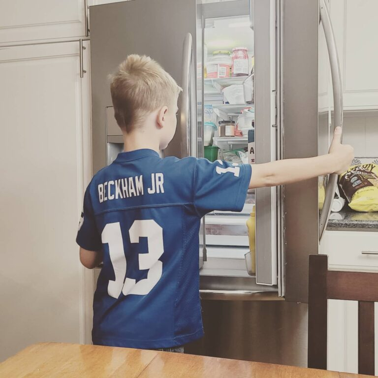 Little boy putting away groceries