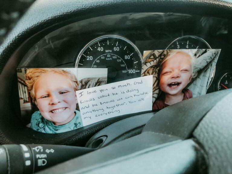 Two photos of children and notecard on dashboard of car, color photo