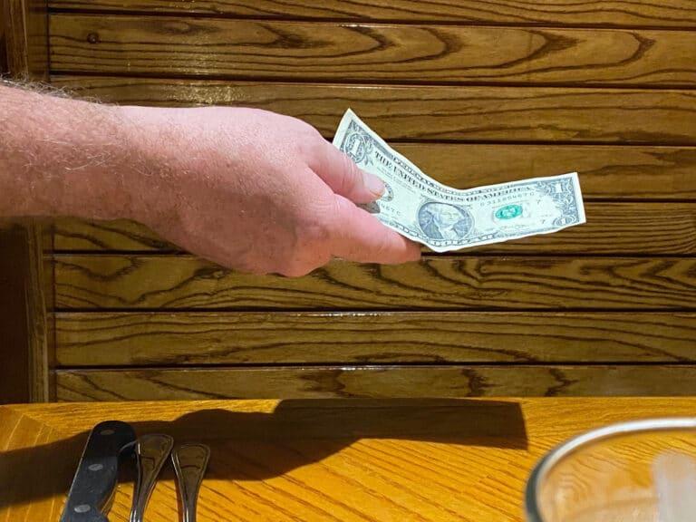 Man handing dollar bill, color photo