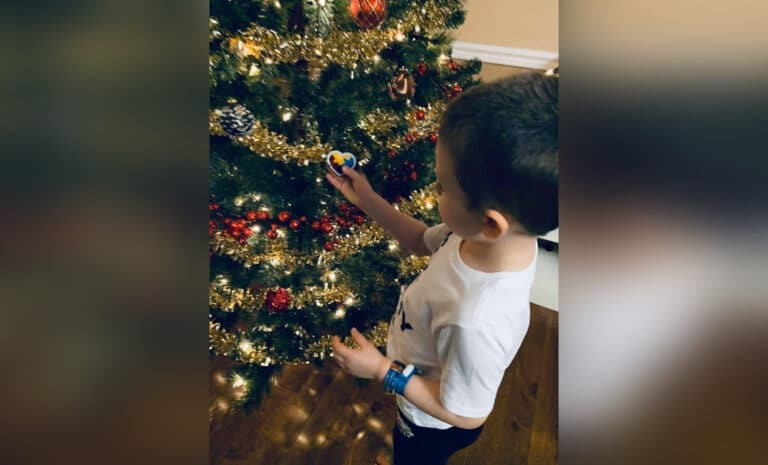 Little boy looking at Christmas tree