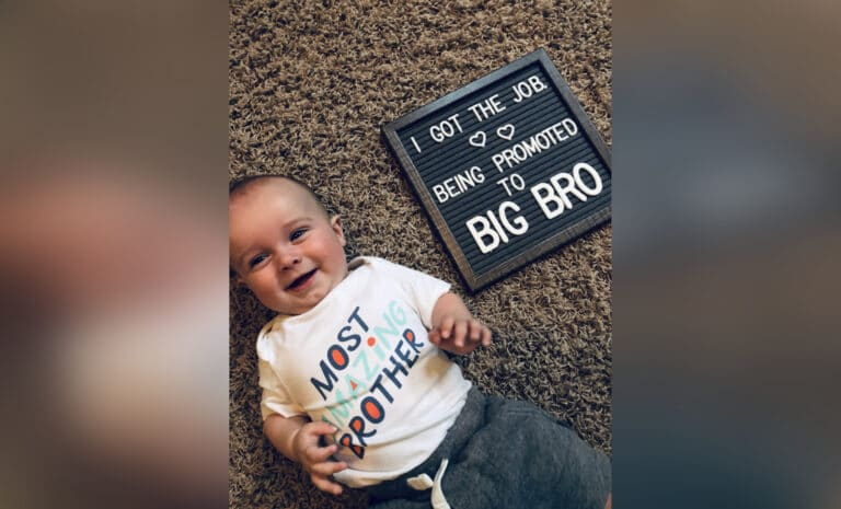 Baby boy next to sign that says big brother, color photo
