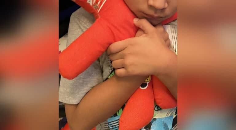 Little boy hugging red bear, color photo
