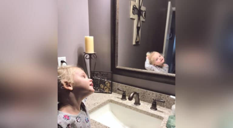 Child looking into mirror, color photo