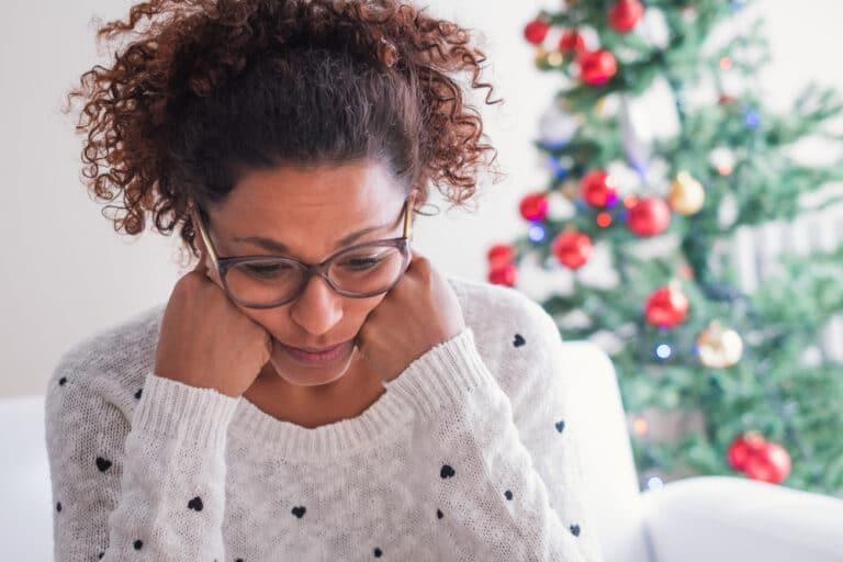 Sad woman by Christmas tree