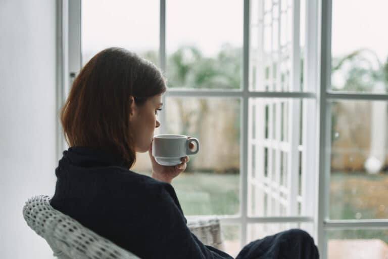 Woman sipping coffee by window