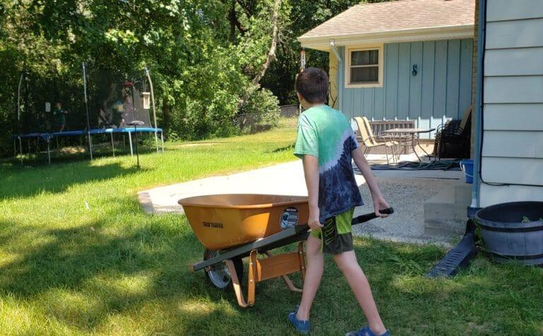 Young boy pushing wheelbarrow, color photo
