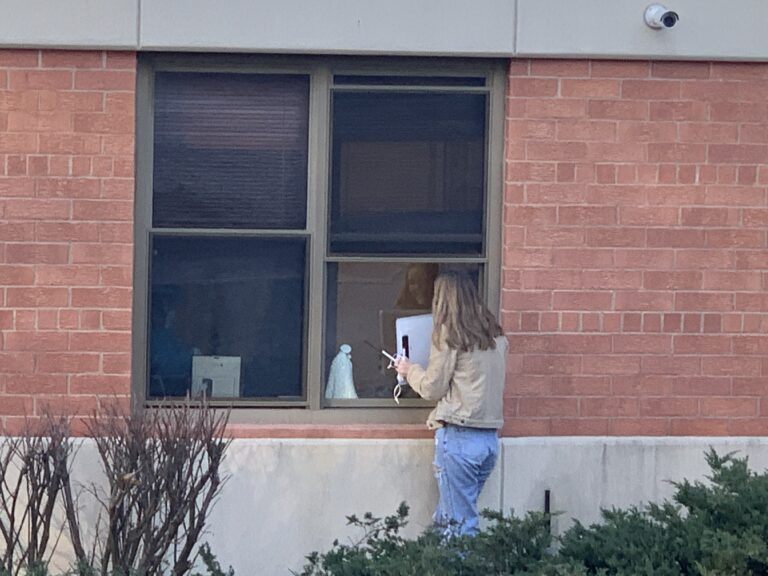 Teen holding up sign to window