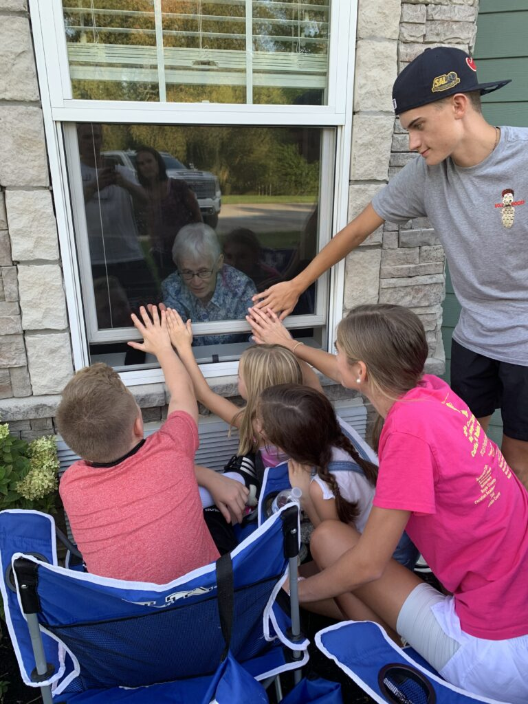 Family gathered around a window, elderly woman inside, color photo