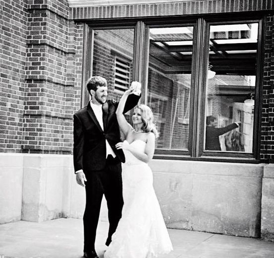 Bride and groom outside of building, black-and-white photo