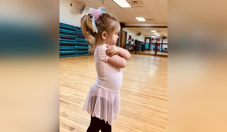 Little girl standing defiantly in dance uniform, color photo