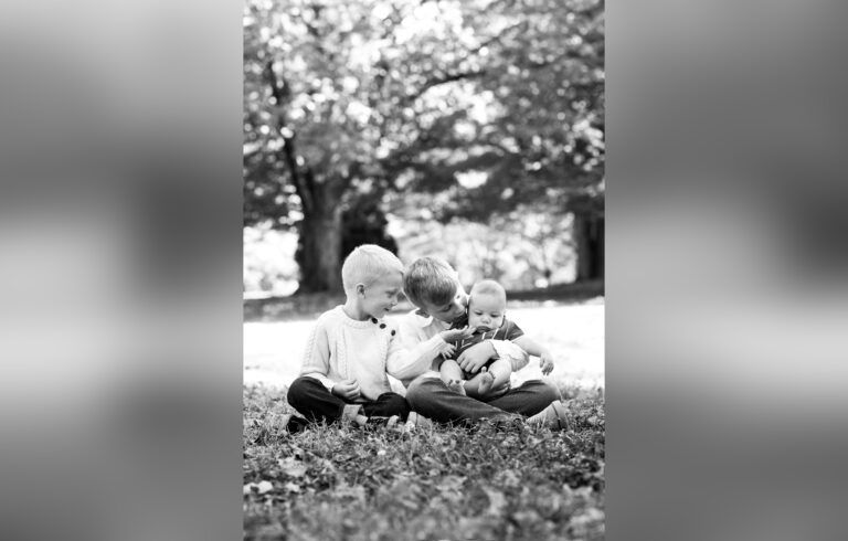 Three children in leaves, black-and-white photo