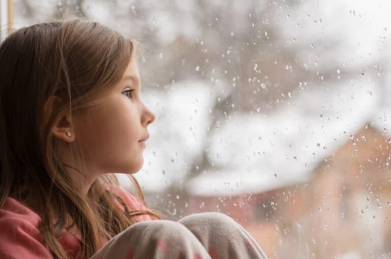 Little girl looking out snowy window