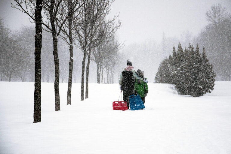 Family walking in snow with sleds