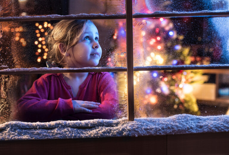 Little girl looking out Christmas window