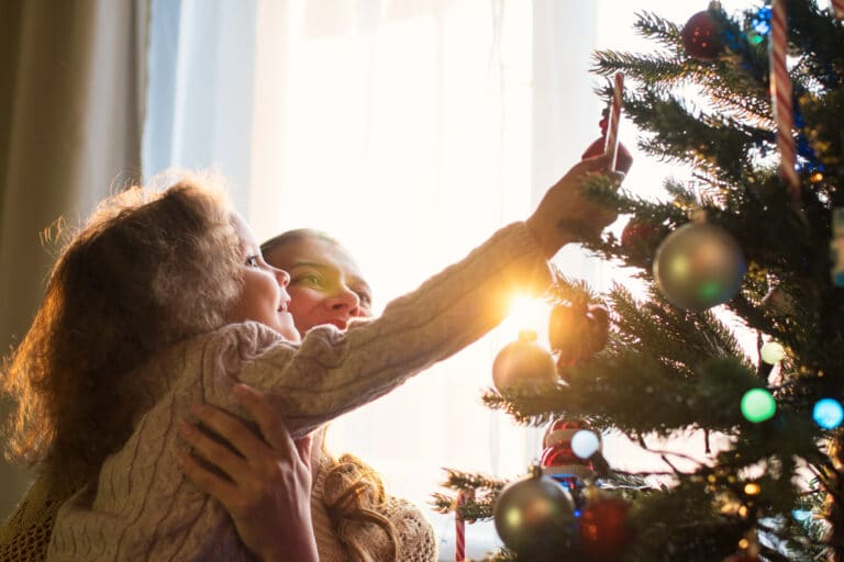Mother and daughter hang ornaments on tree