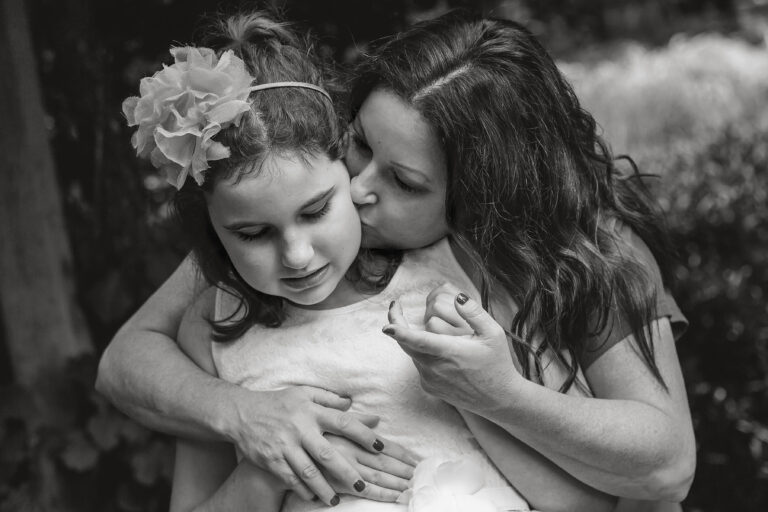 Mother kissing daughter, black-and-white photo