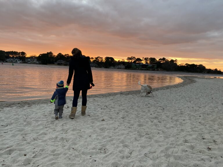 Mother and son walking on beach, color photo