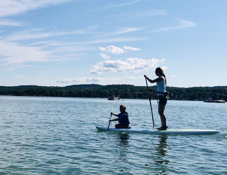 Boy and woman standing on paddle board, color photo