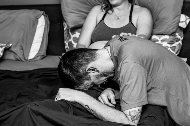 Man crying on wife's lap, black-and-white photo