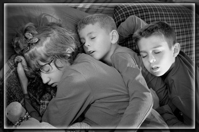 Two young boys hugging their sister, black-and-white photo