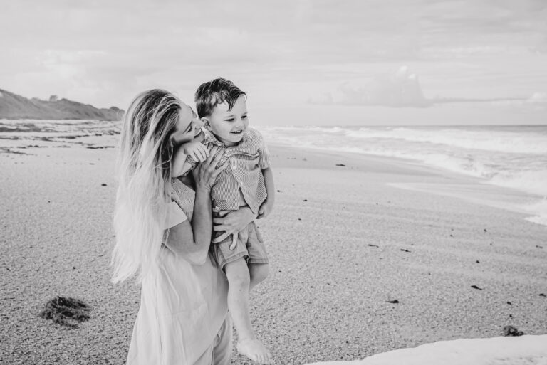 Mother holding son on beach, black-and-white photo