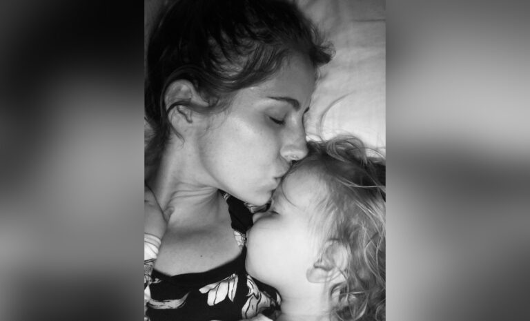 Mother kissing child, black-and-white photo