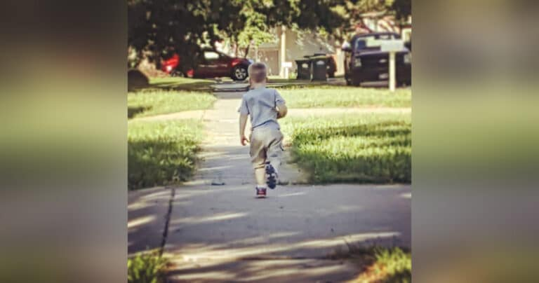 Young boy walking down sidewalk, color photo