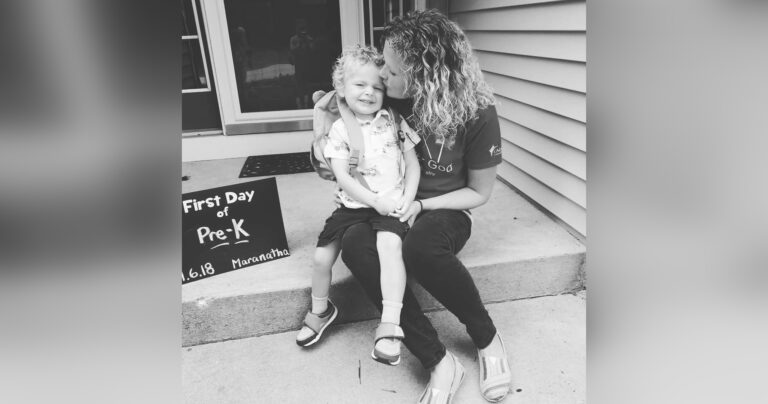 Mother kissing son next to first day of pre-k sign, black-and-white photo