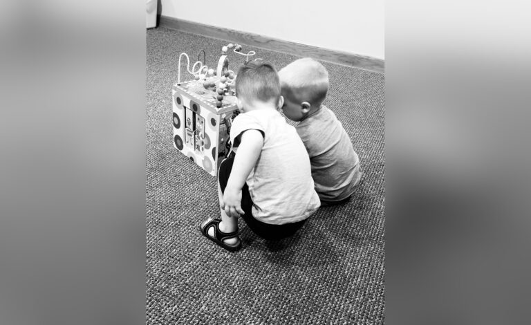 Two boys playing together, black-and-white photo