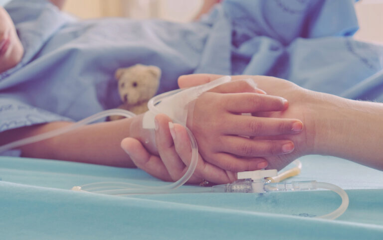 child hand in hospital bed