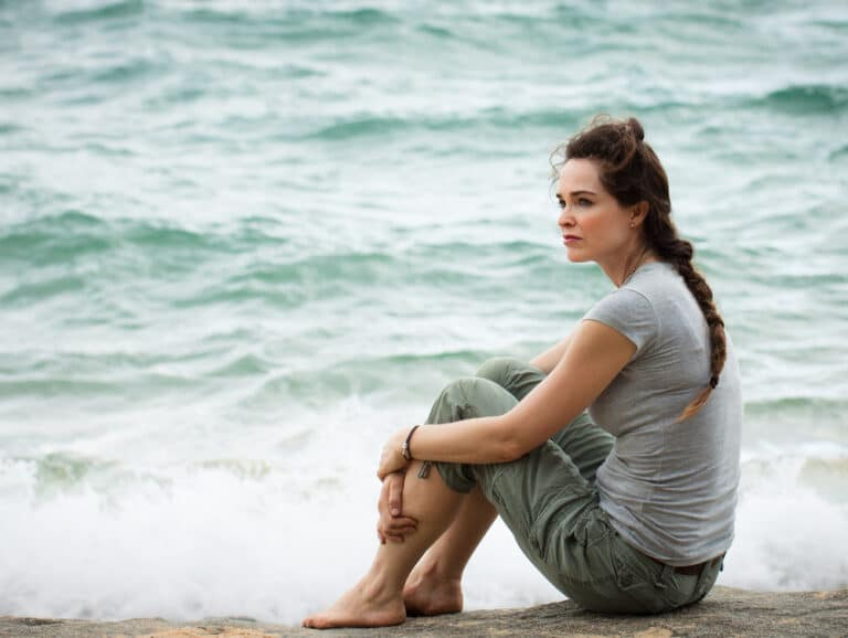 Woman sitting by sea