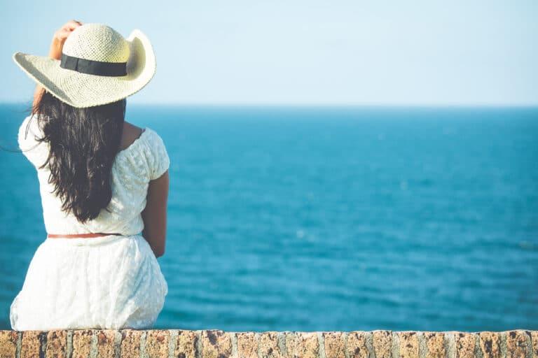 Woman sitting by ocean