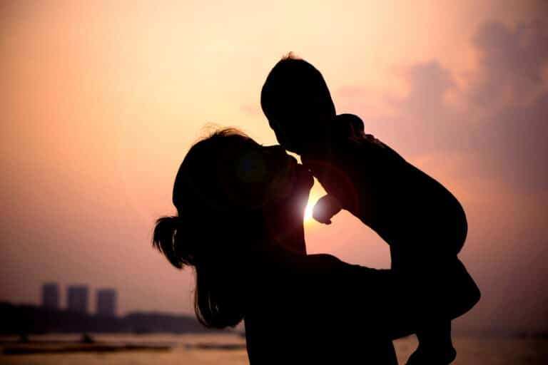Mother holding up child in sunset