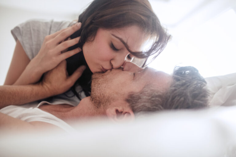 Woman kissing man on bed